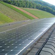 Solar panels on a building near a farm