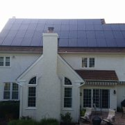 House with solar panels on back side of roof